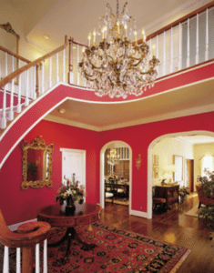 The sweeping staircase and exquisite lighting highlight the dramatic red walls. This is an entry where guests feel the warmth of the house.