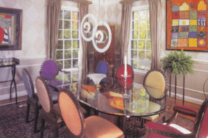 The unexpected becomes understated elegance with chairs of many colors surrounding the leather-framed, serpentine table of inlaid bird's eye maple. Luna Lighting pendants create a focal point of the room while the soft, hand-painted diamond wall pattern provides a neutral backdrop for artwork Pelley selected in Goree Island, West Africa while traveling with President Clinton.